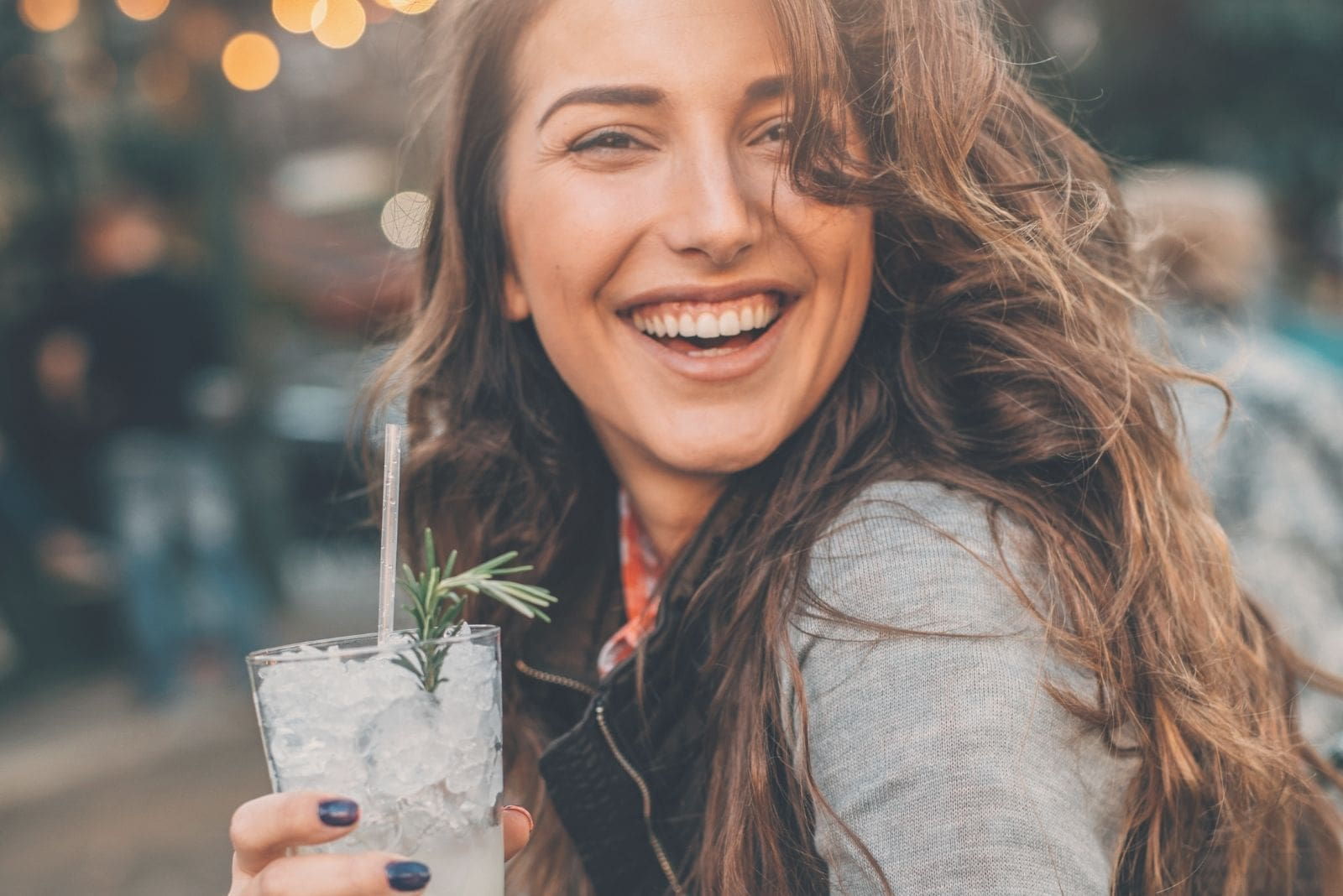 beautiful young woman drinking cocktails and smiling outdoors