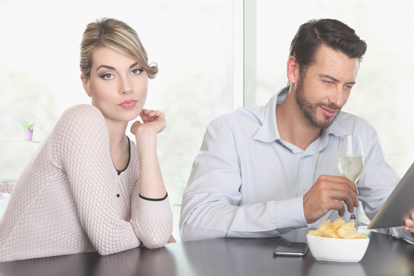 bored woman sitting beside an indifferent person busy with his tablet while inside a cafe