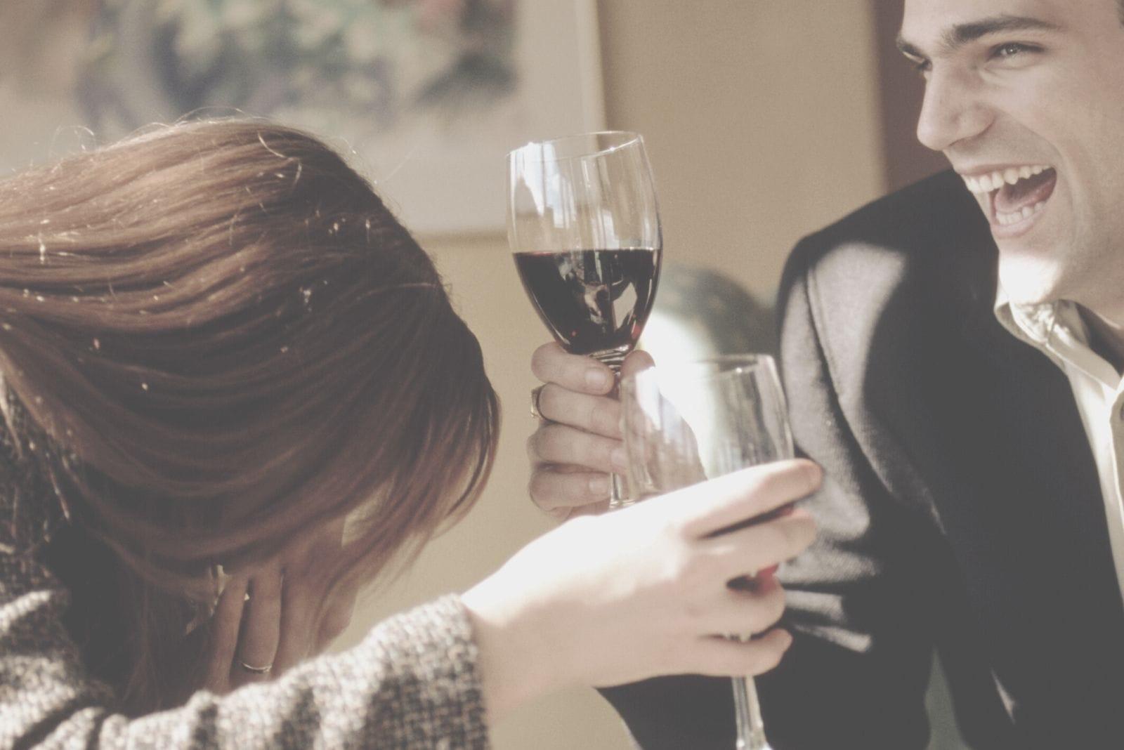 cheerful couple drinking wine laughing hard