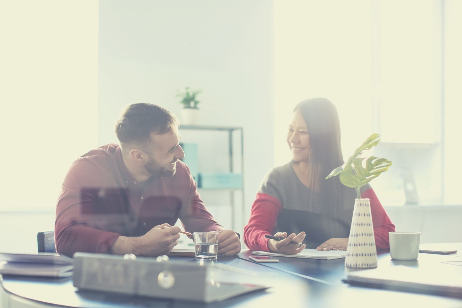 cheerful man and woman talking inside the office
