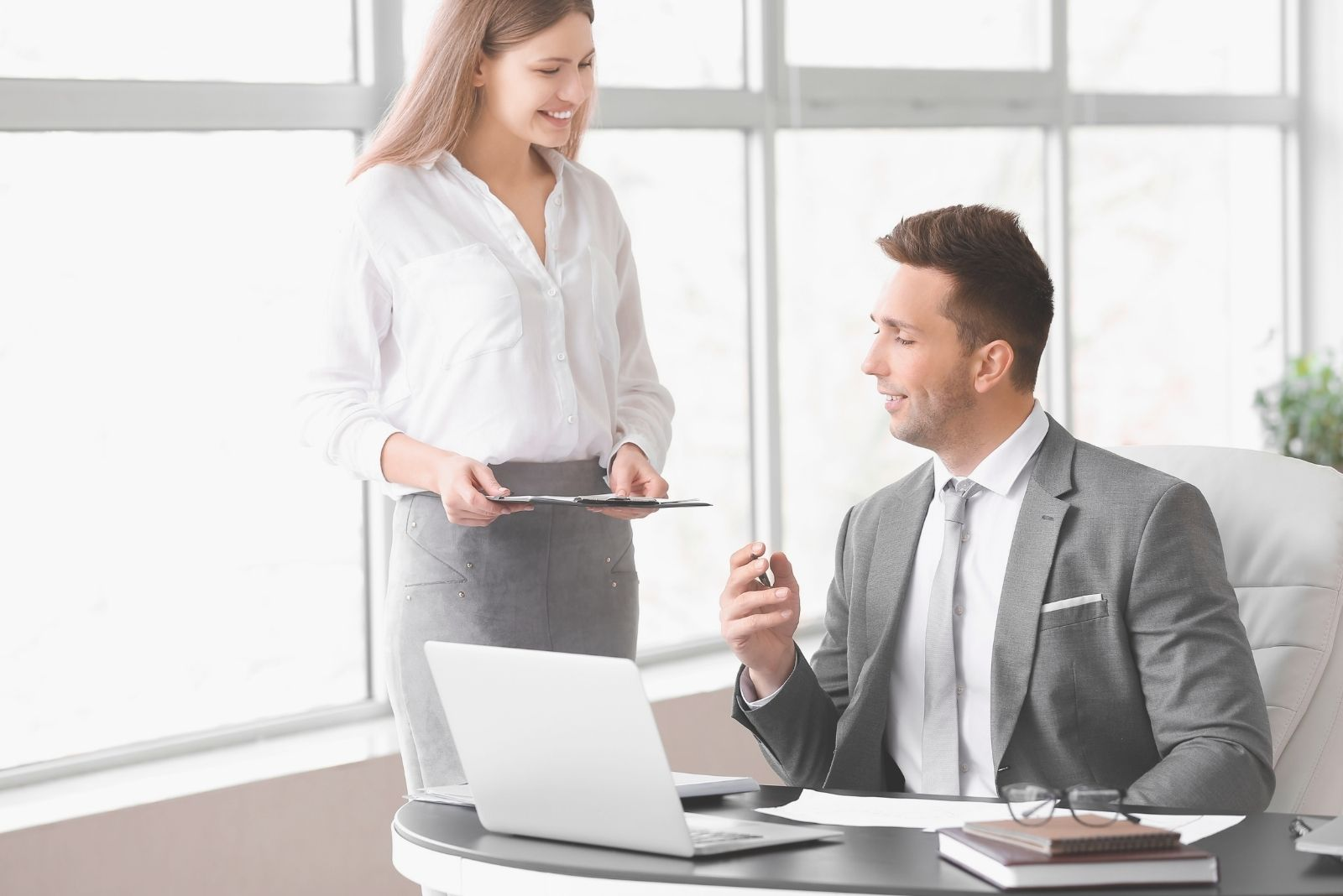 colleagues working in office with the woman standing near the man sitting by his office table
