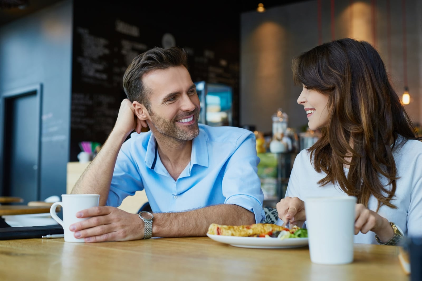 man and woman drinking coffee while having lunch