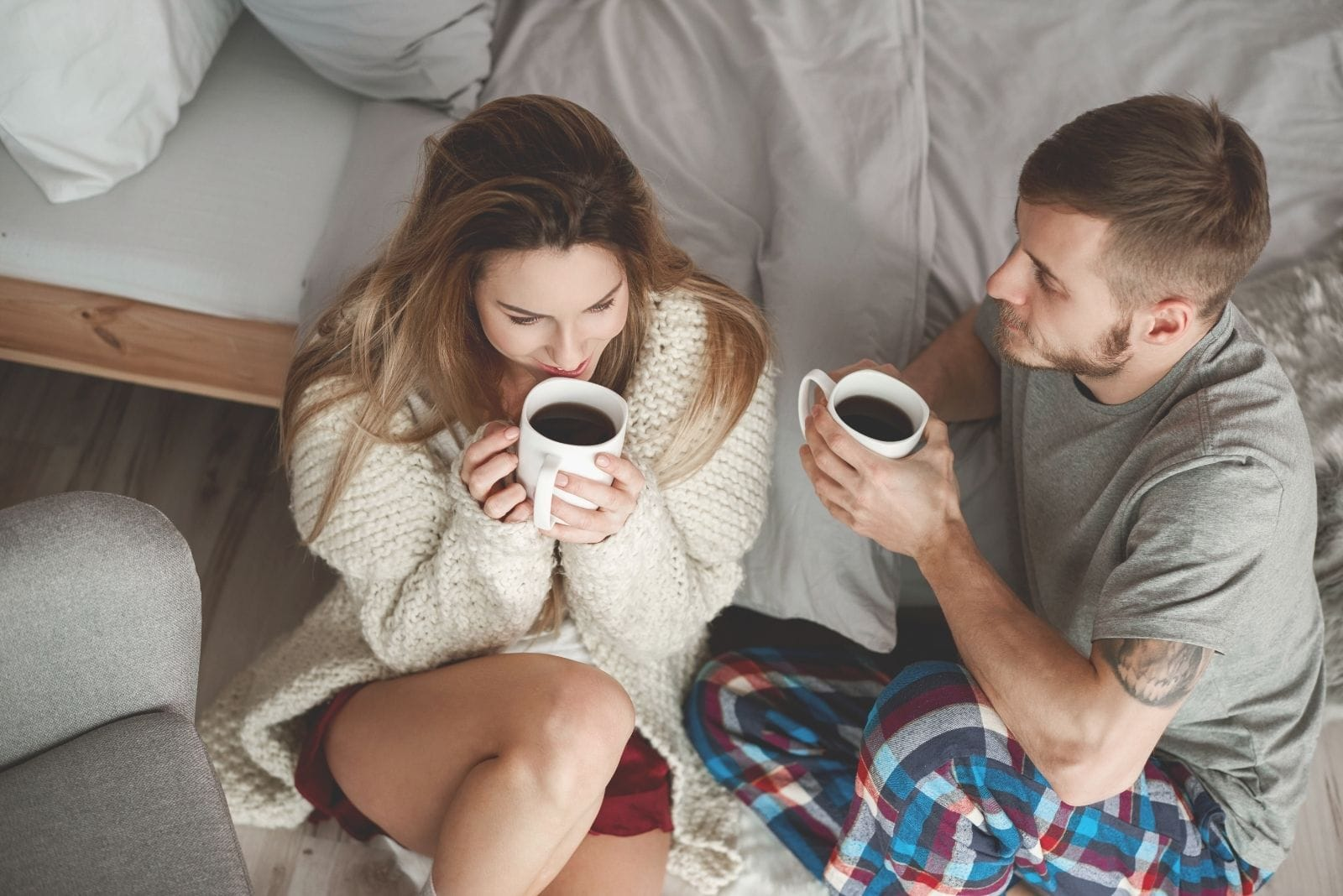 couple drinking morning coffee beside the bed on the floor