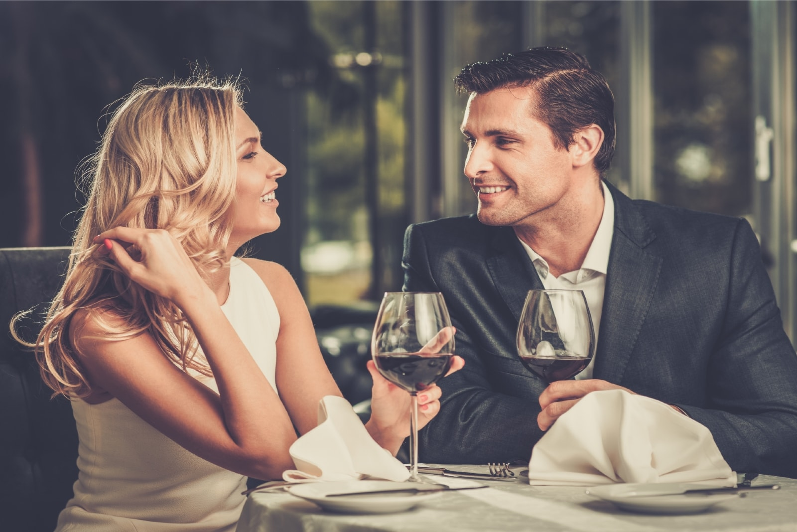 happy man and woman drinking wine while sitting at table