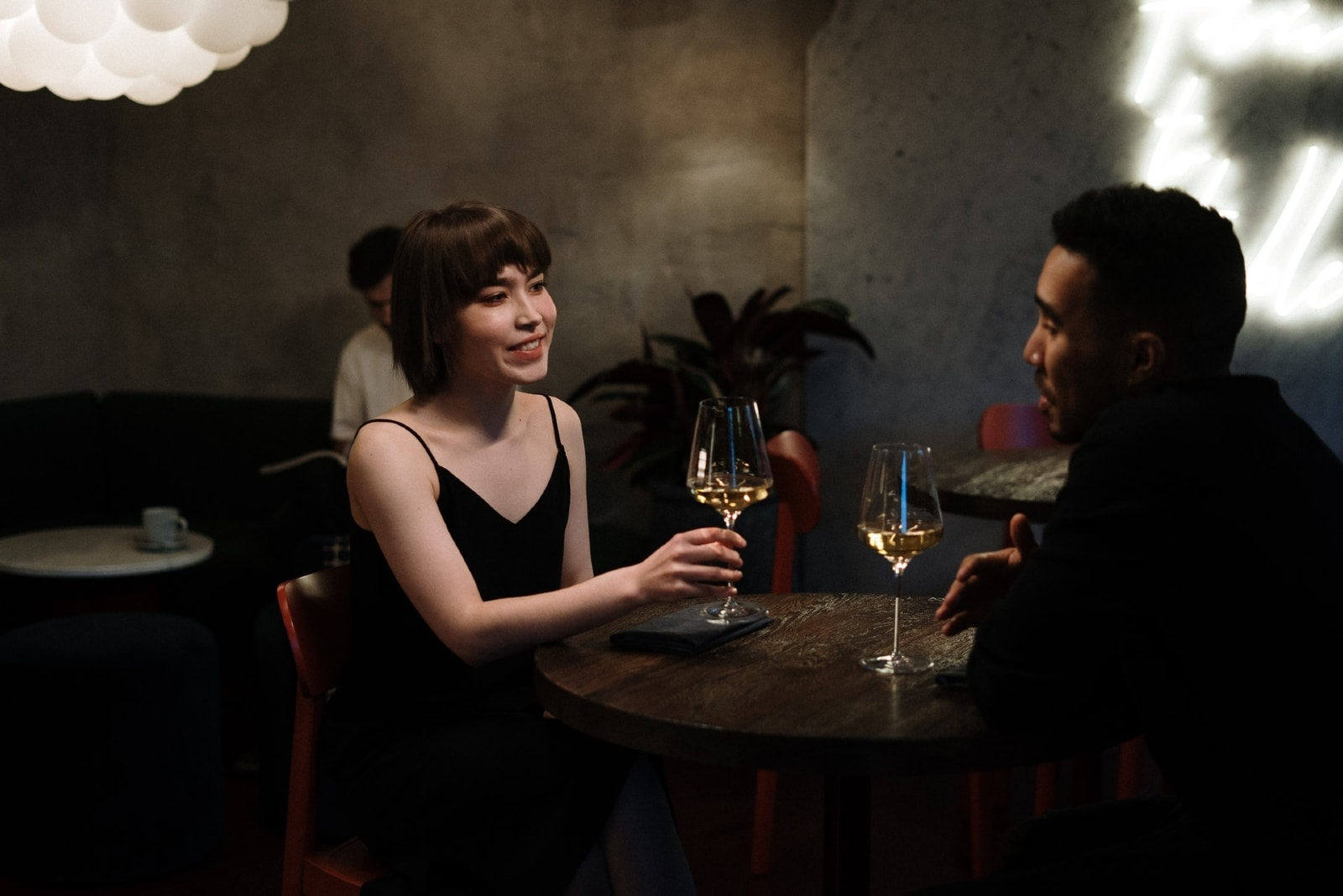 man and woman drinking wine while sitting at table