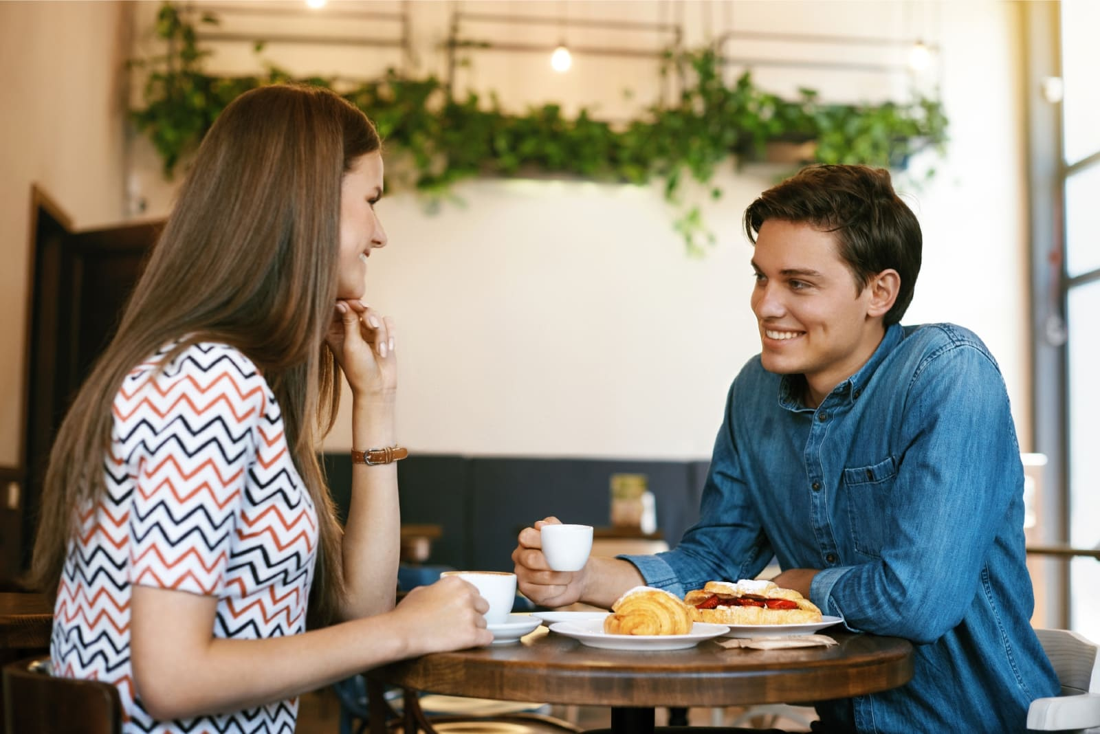 man and woman having coffee while sitting in cafe