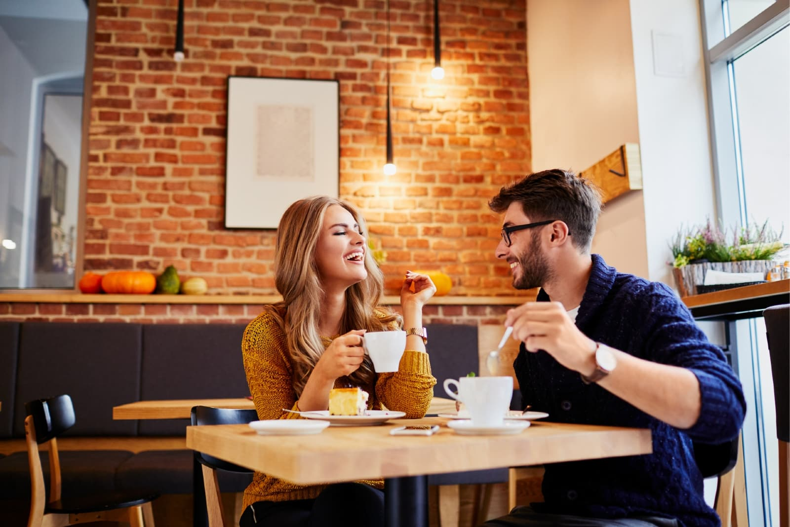 man and woman eating and having coffee