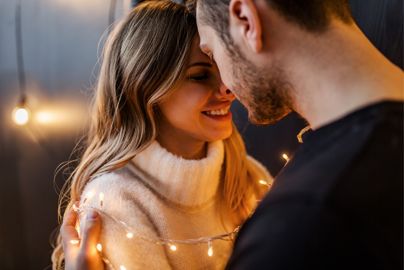 happy woman in white turtleneck sweater and man hugging indoor