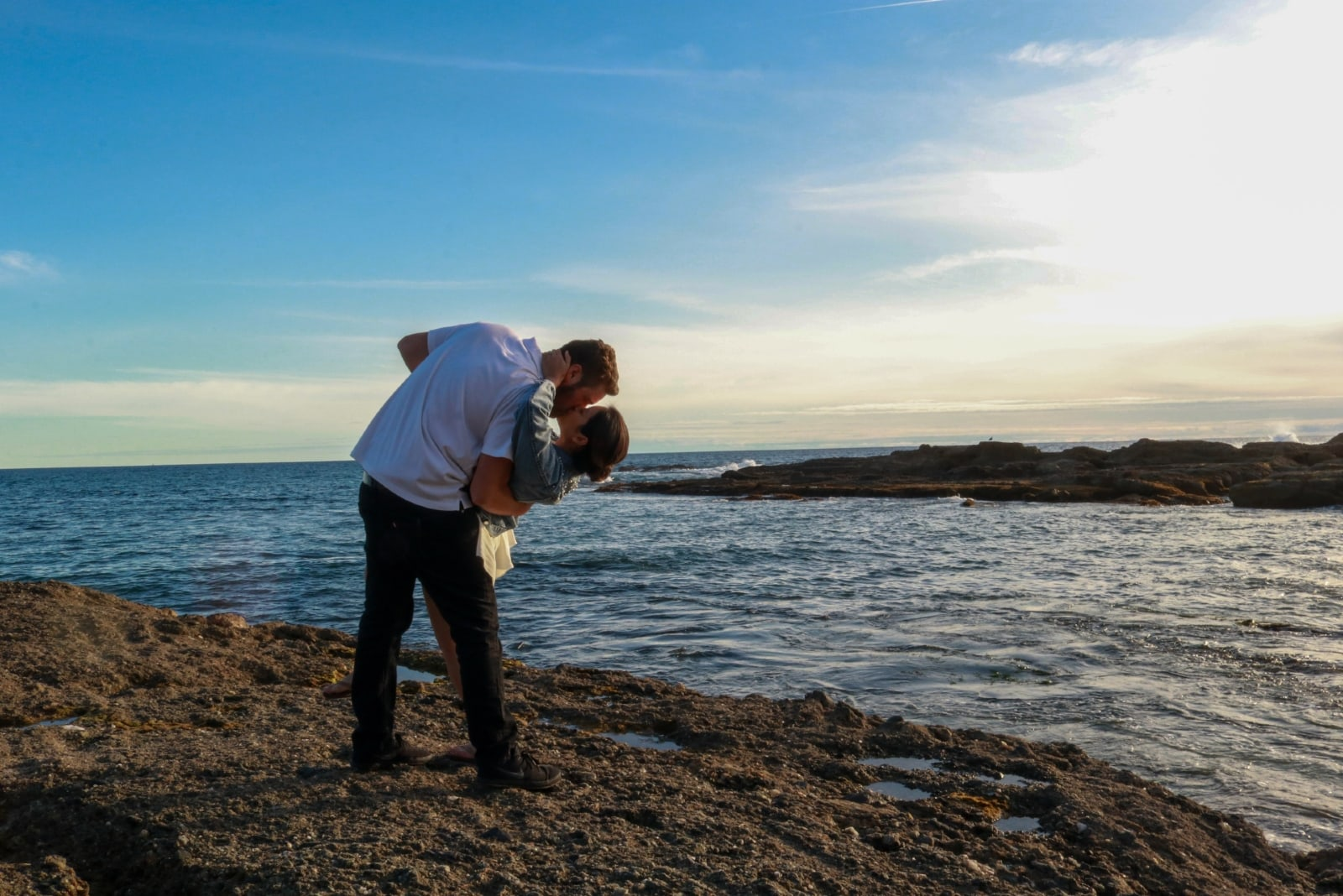 man and woman kissing while standing near sea