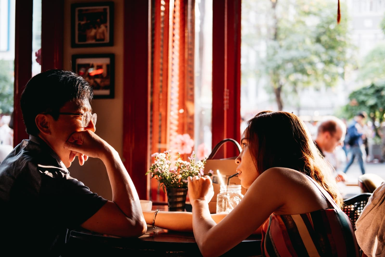 man and woman making eye contact while sitting in cafe