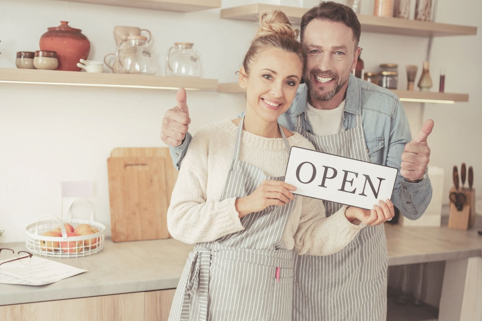 couple openning a business holding the word open wearing apron