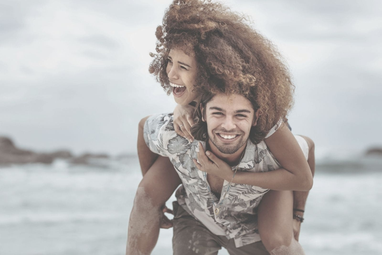couple piggybacking and laughing near the sea