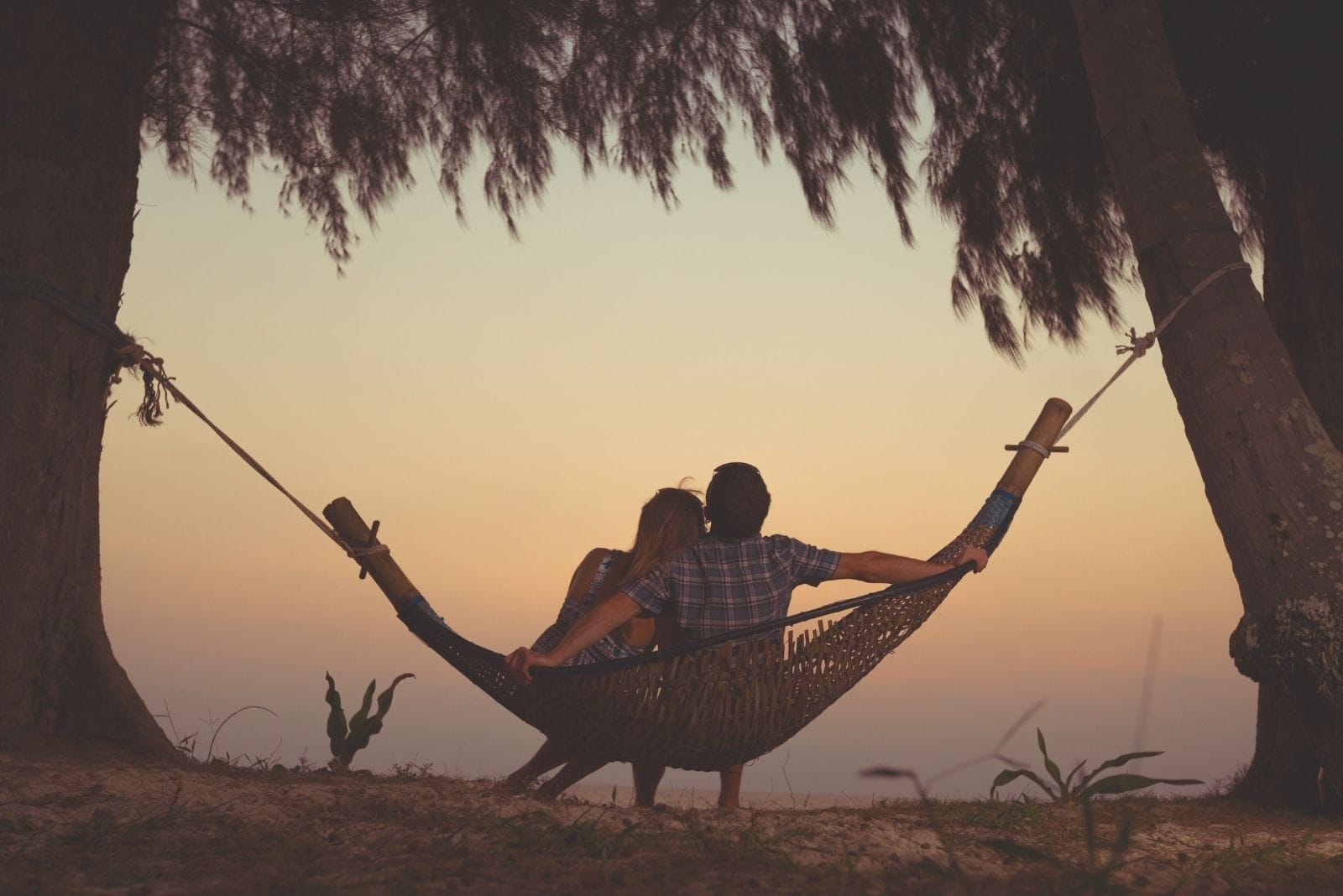 couple relaxing in a hammock hanged on trees facing the clouds on golden hour