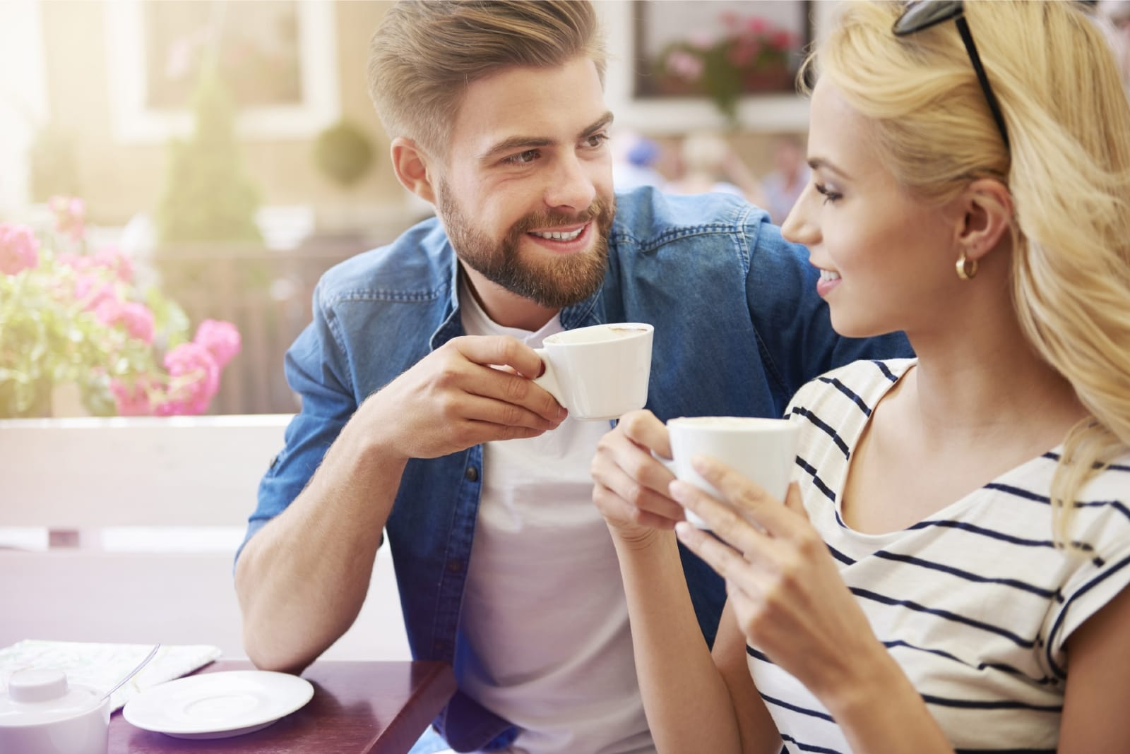 man and woman having coffee while sitting at table