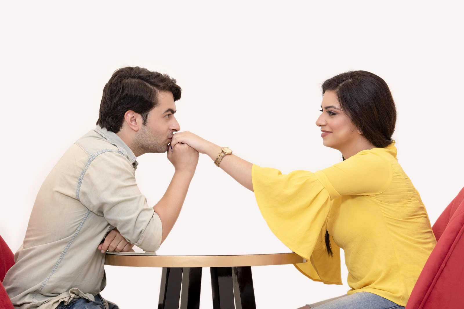 man kissing woman's hand while sitting at table