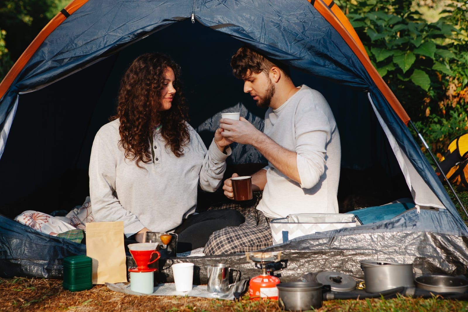 man and woman having coffee while sitting in tent