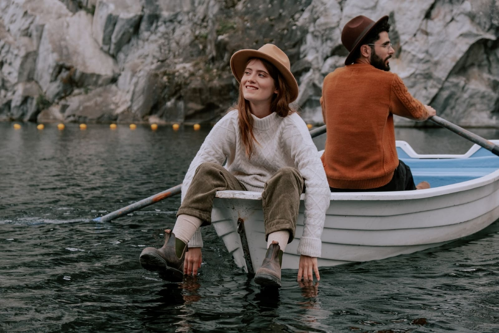 man and woman with hats sitting on boat