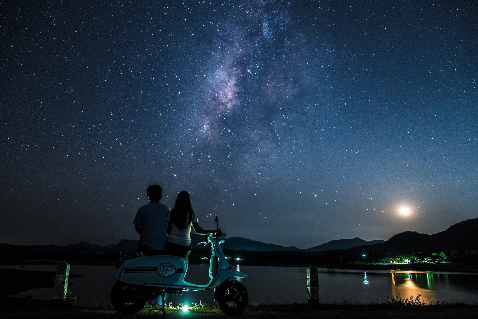 man and woman sitting on motorcycle looking at stars