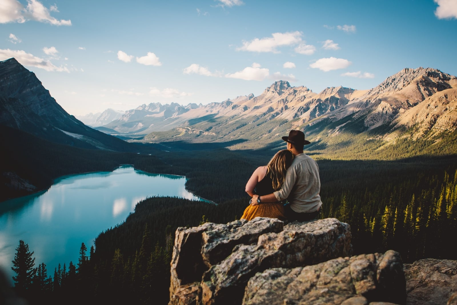 man and woman looking at lake while sitting on rock