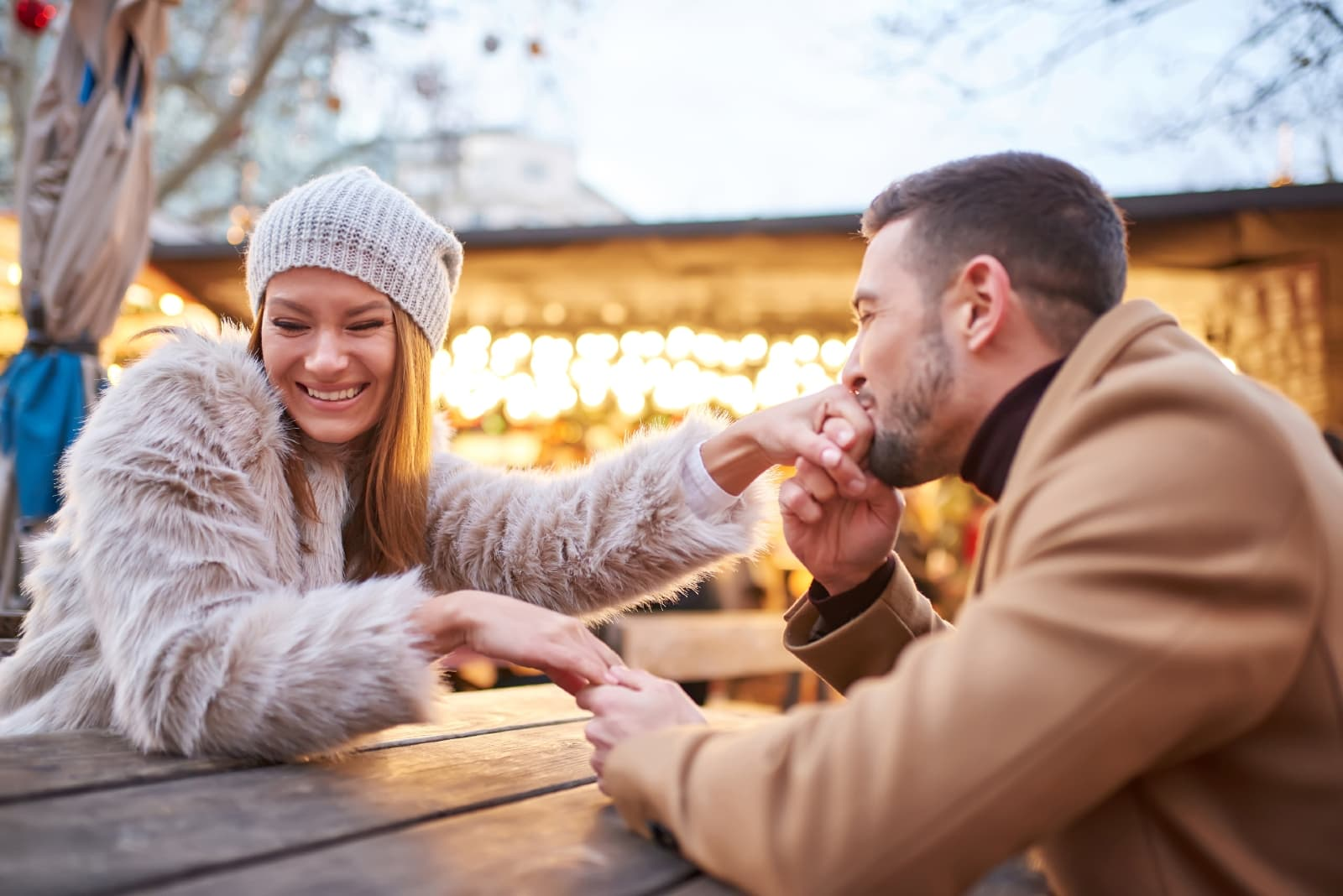 happy man kissing woman's hand while sitting outdoor