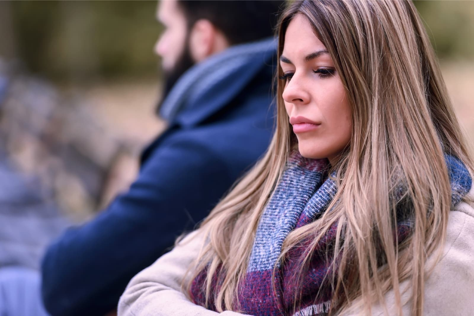 sad woman with scarf sitting near man outdoor