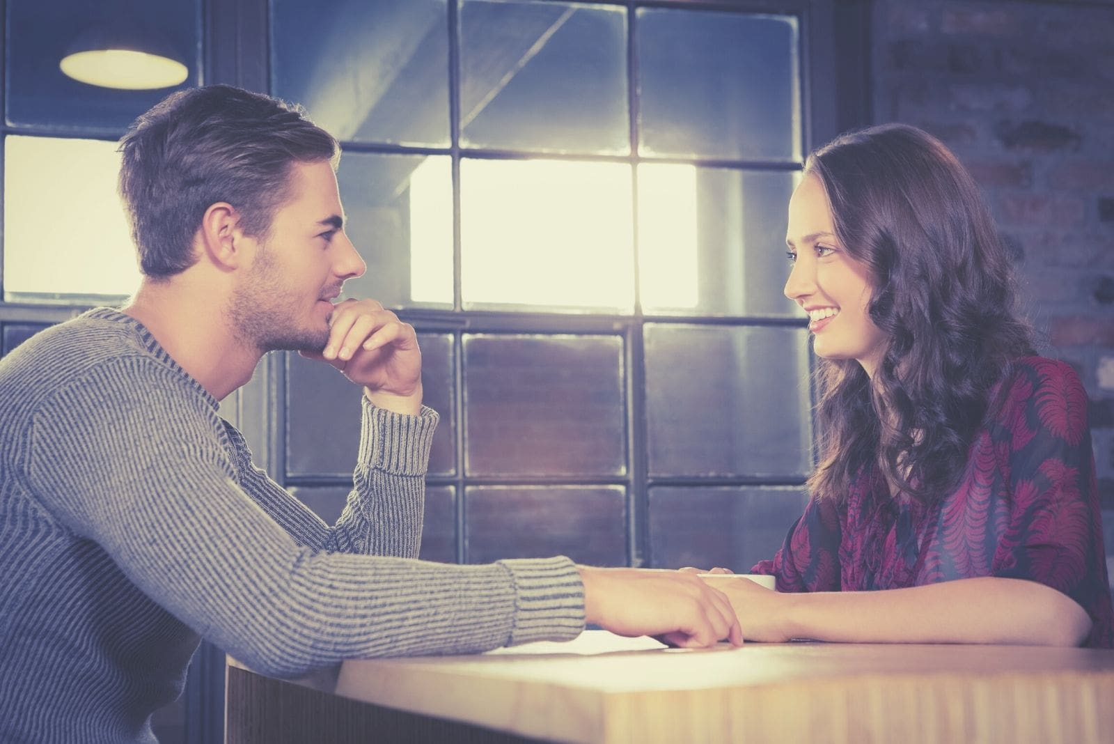 dating couple talking and smiling at a restaurant