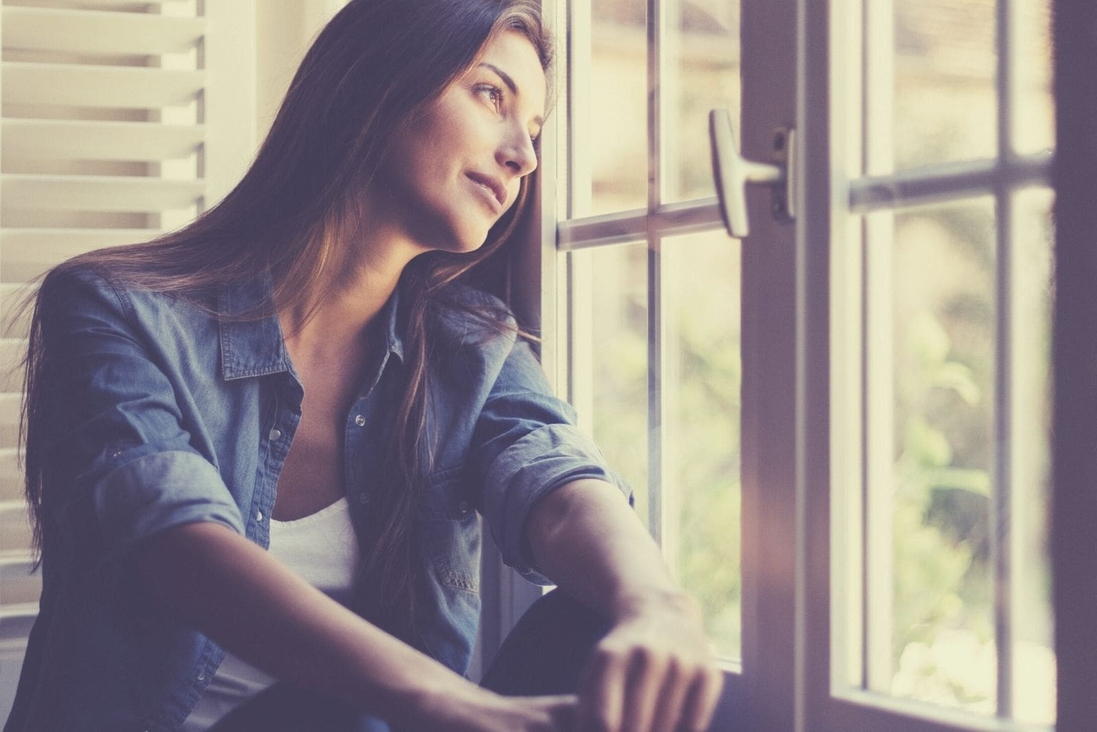 dreamy woman at the window smiling and sitting wearing a denim jacket