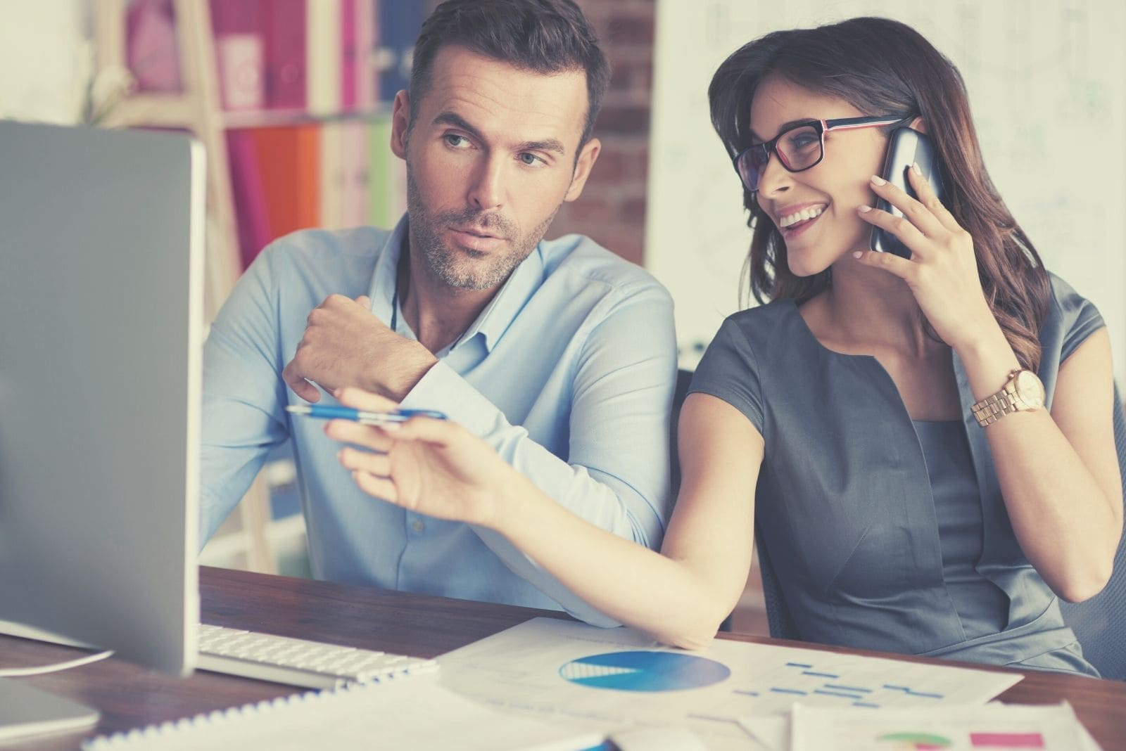 female colleague giving good advice to a male colleague regarding his work in the computer while answering phone