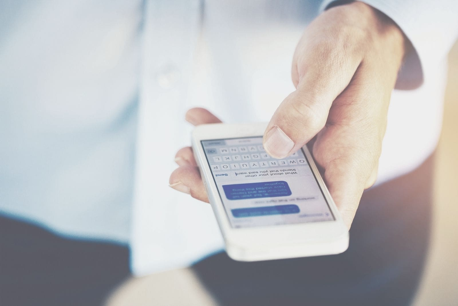 focused photography of a man's hand holding a phone and texting