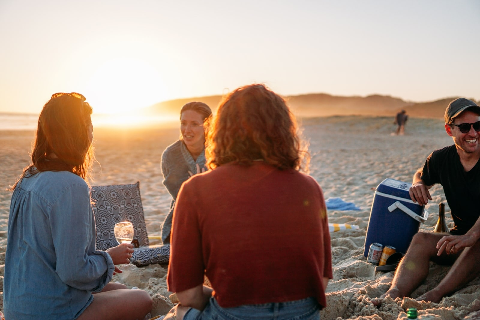 friends talking while sitting on sand