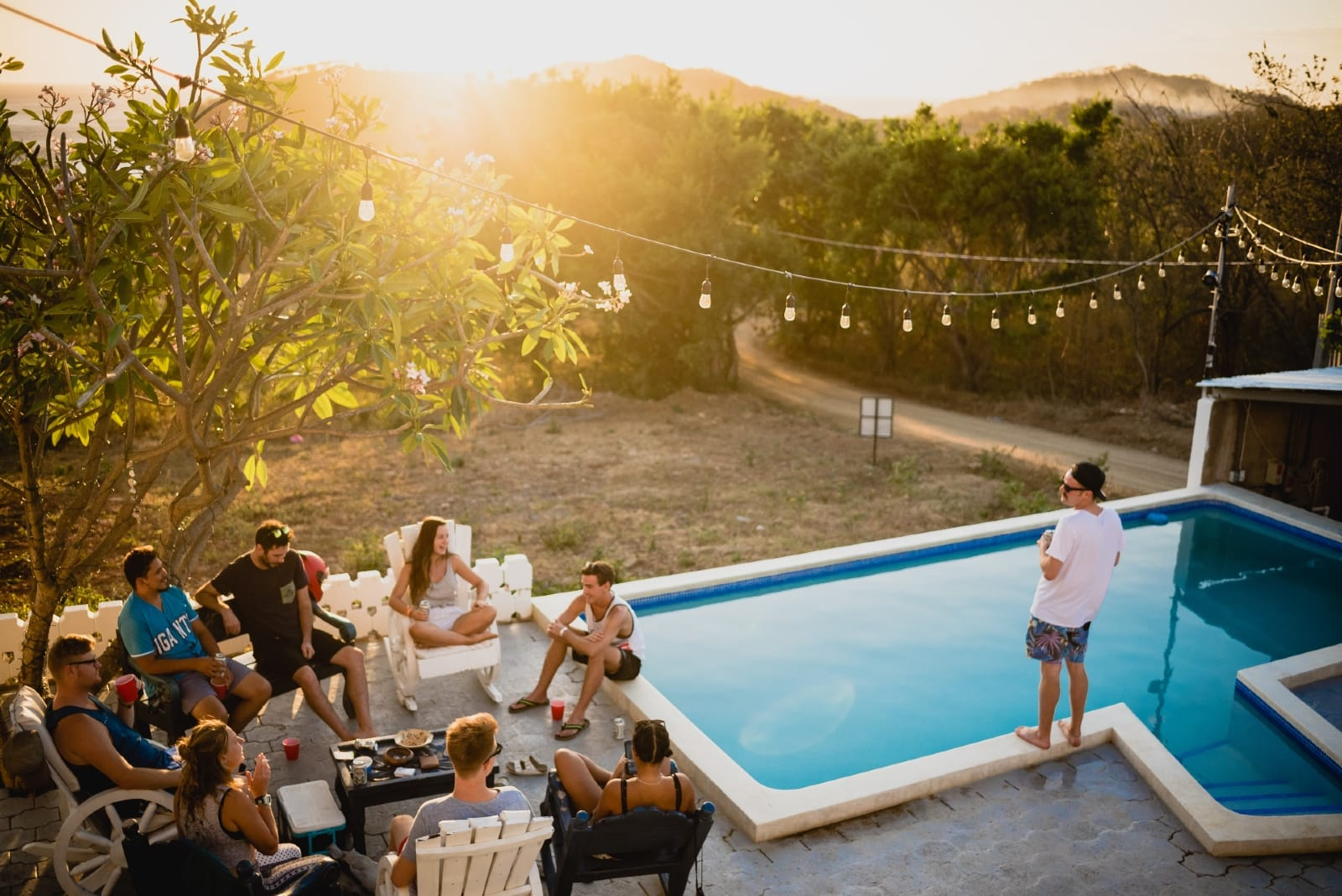 friends talking while sitting near pool