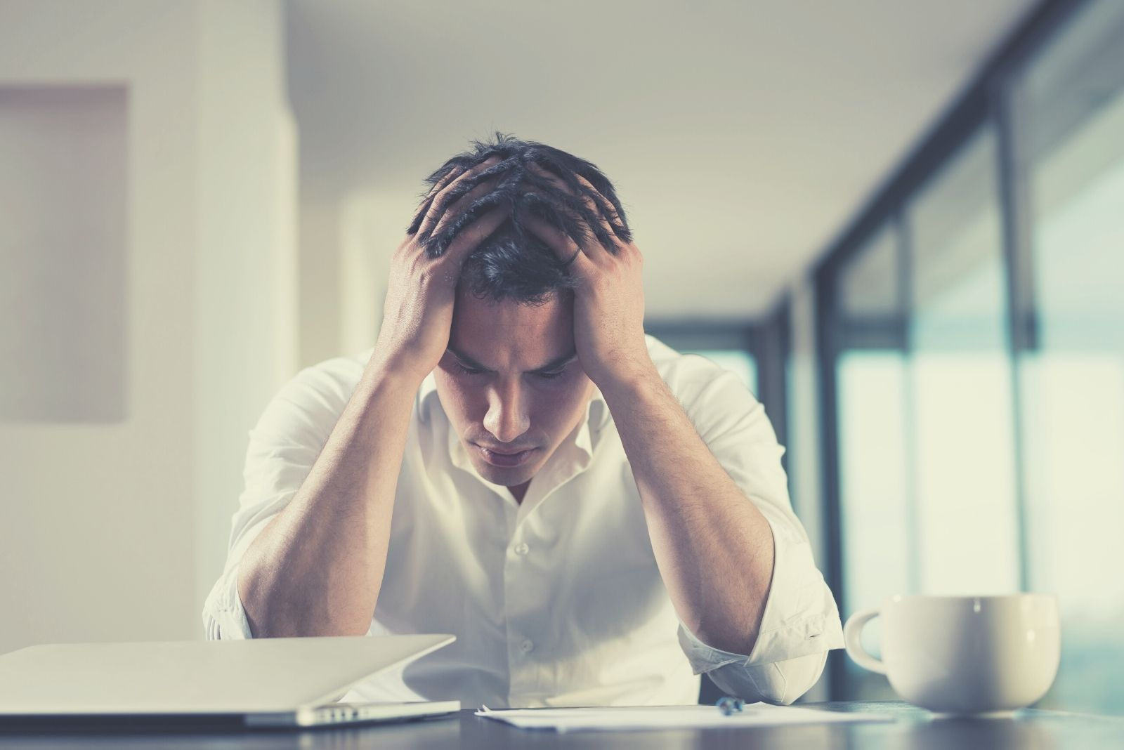 frustrated with problem man working in his laptop inside office with hands in his head
