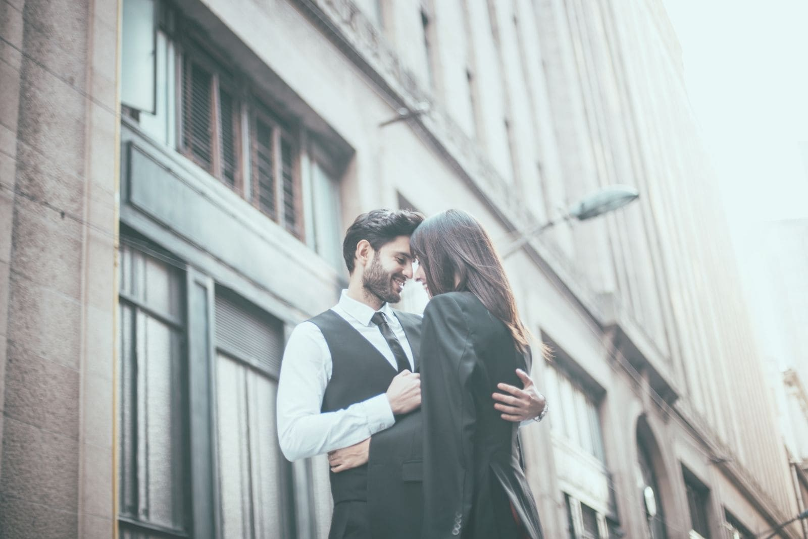 handsome gentleman in suit hugging a woman outdoors