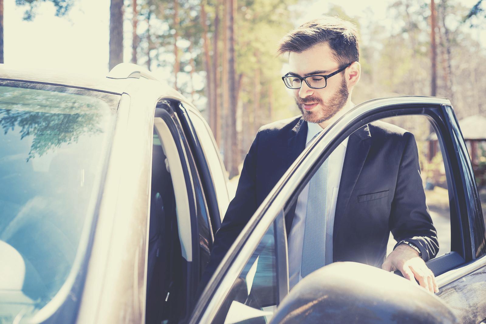 happy businessman sliding inside the car outdoors