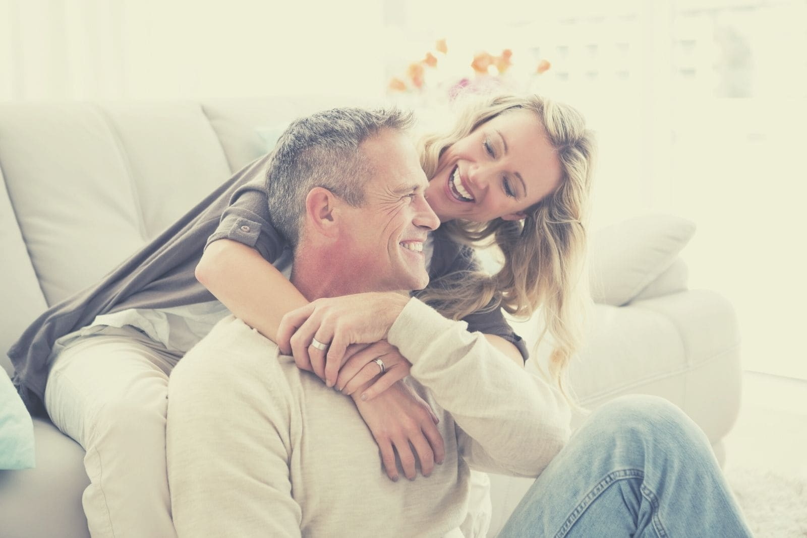 happy couple cuddling in living room while man sitting on the floor