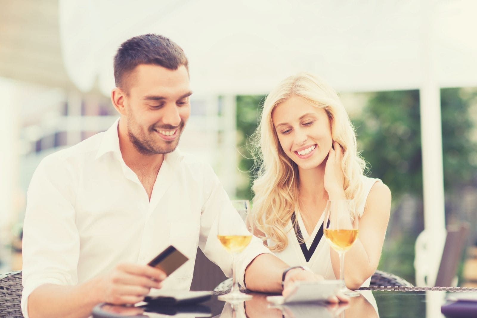 happy couple dating looking at the score card or credit card and smiling