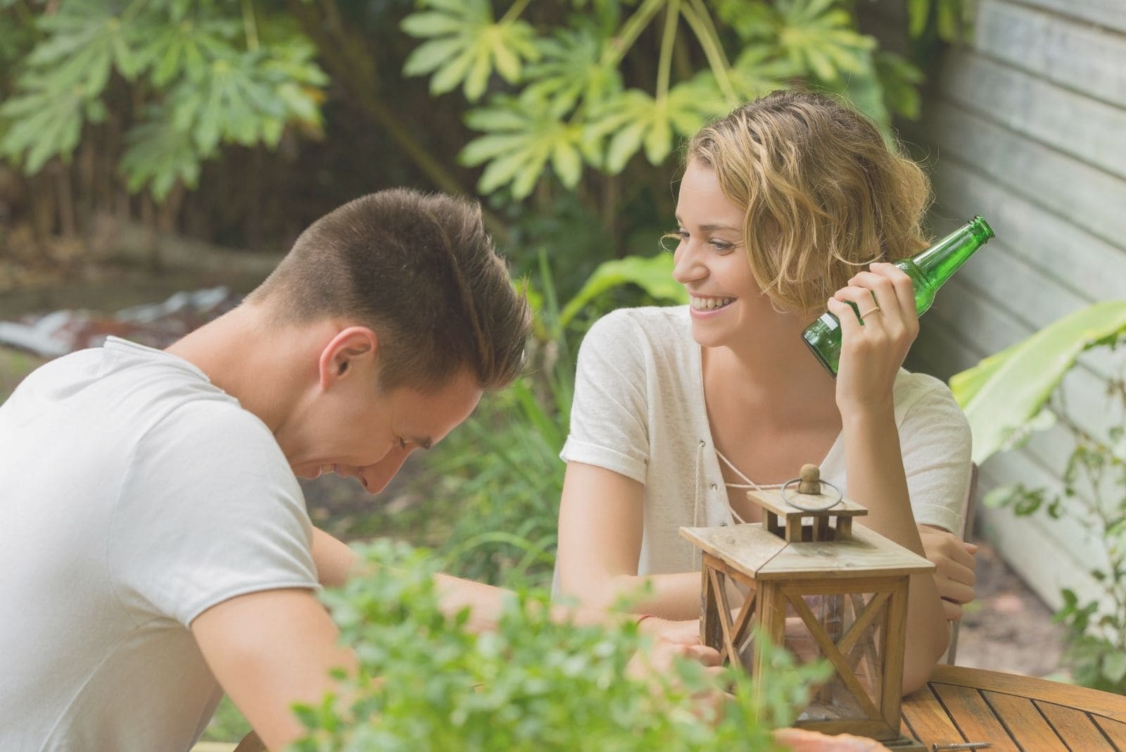 happy couple drinking beer outdoors laughing