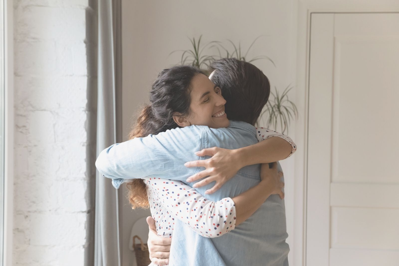 happy couple embracing each other after reconciling inside the house