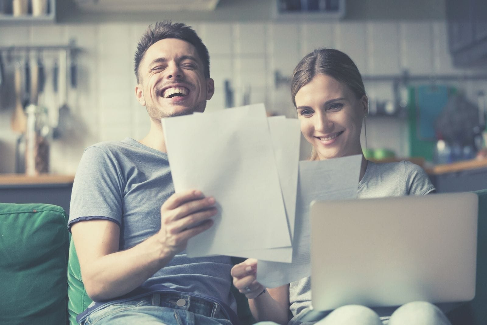 happy couple holding papers and looking at the laptop inside the livingroom