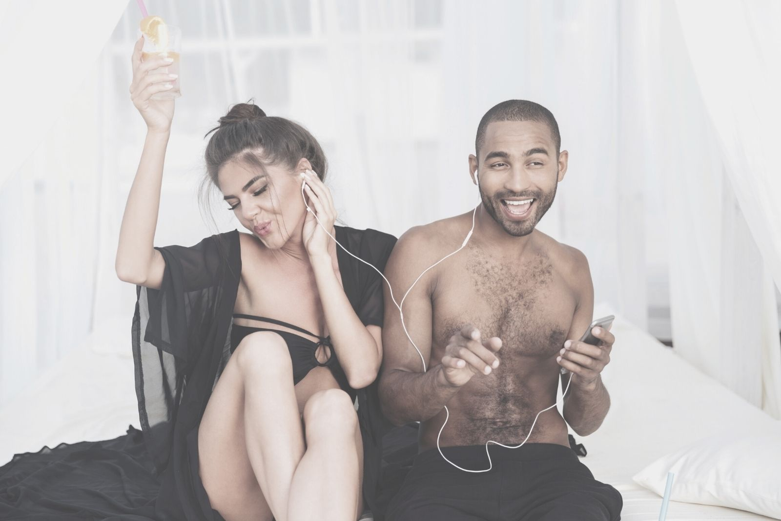 happy couple singing while listening to their earphones in the beach