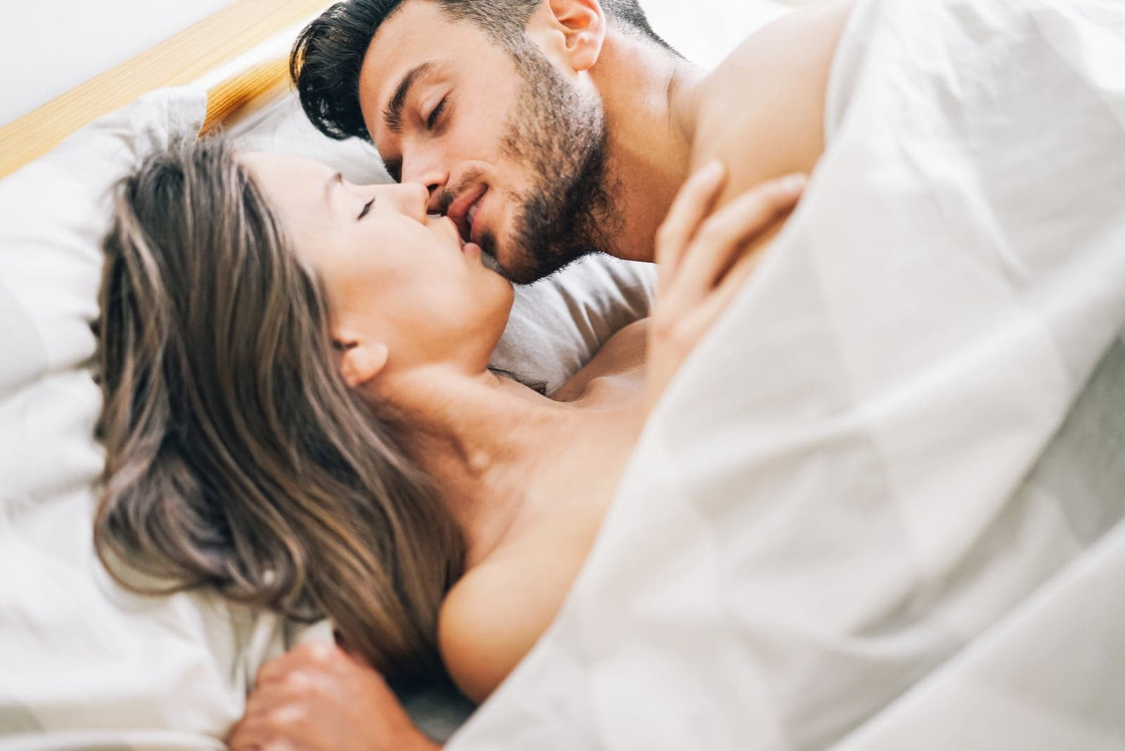 happy man kissing woman under the blanket