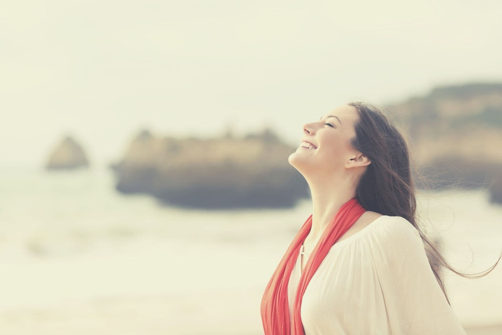 happy woman breathing deeply standing on the beach