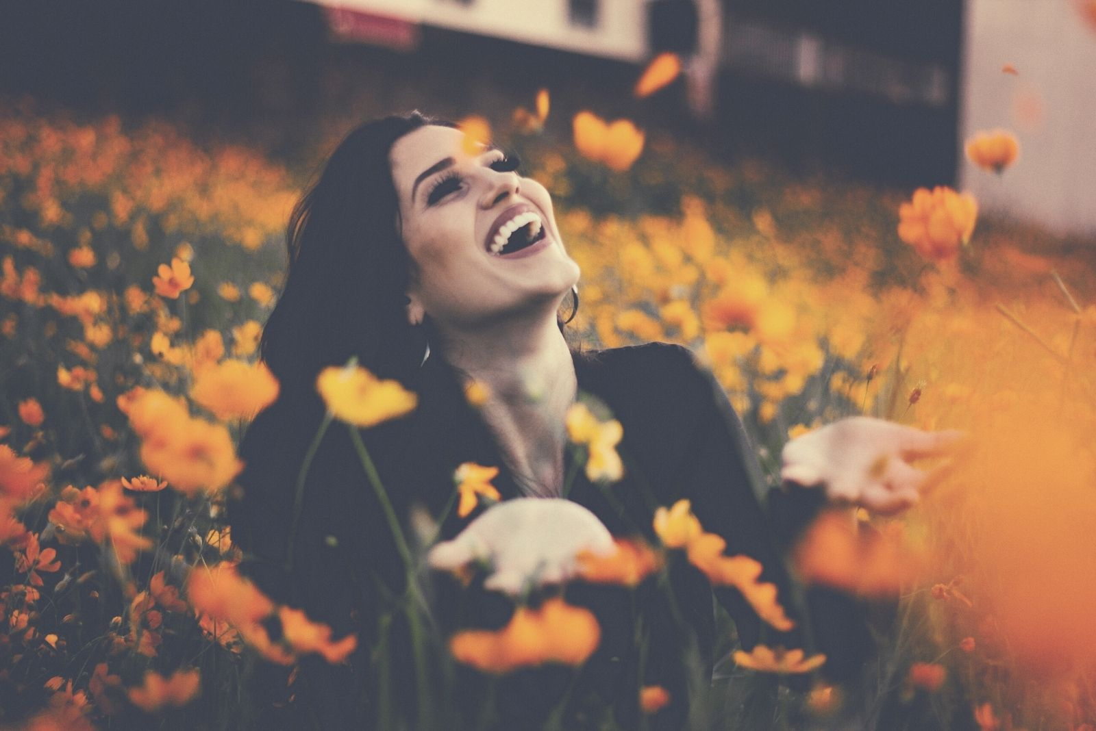 happy woman in flower field playing with orange petal flowers