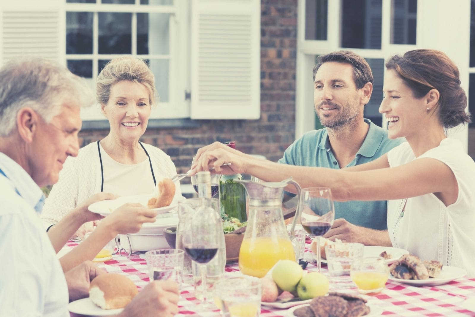 happy woman serving food to elder parents while enjoying meal outdoors