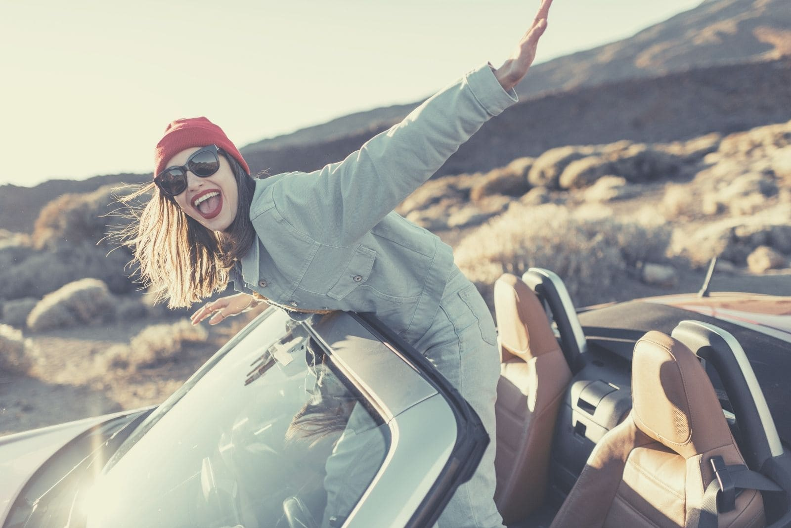 happy woman travelling by an open top down car standing on the seat