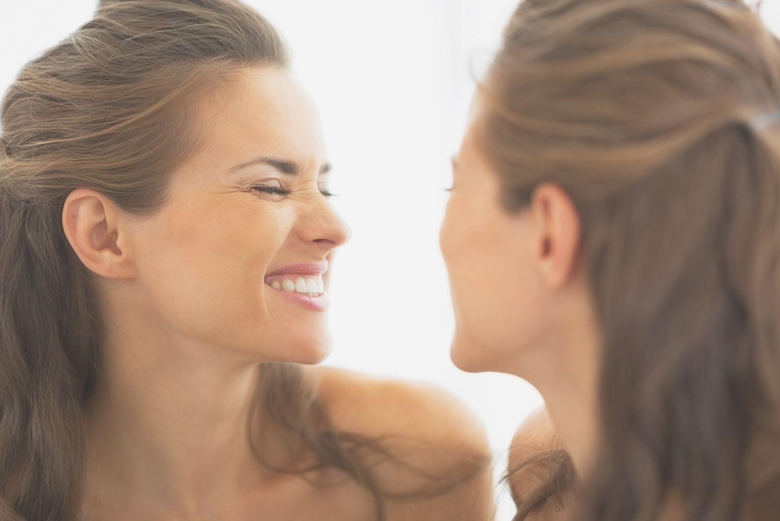 happy young woman making funny face in front of the mirror