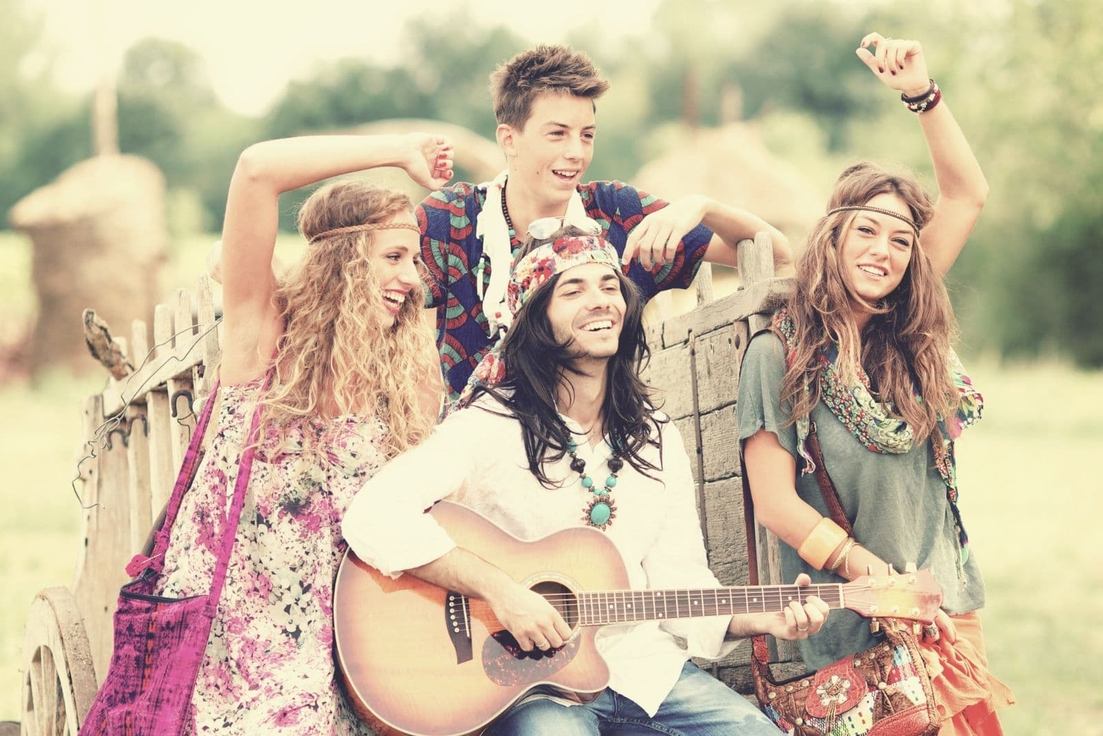 hippies having fun outdoors singing and playing guitar