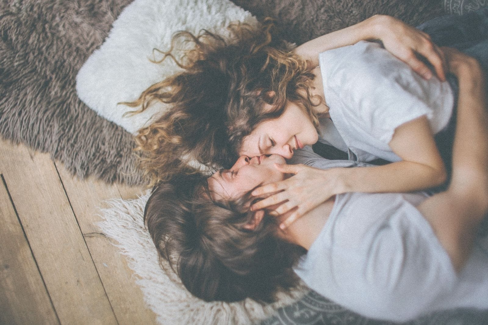 image of a couple in love lying down on the floor on a floormat