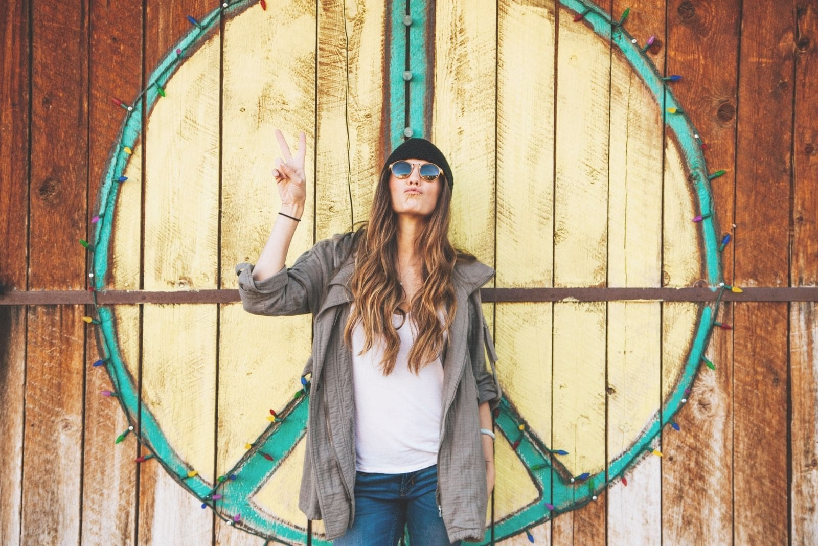 image of a hippie fashion woman standing in a barn door wearing shades