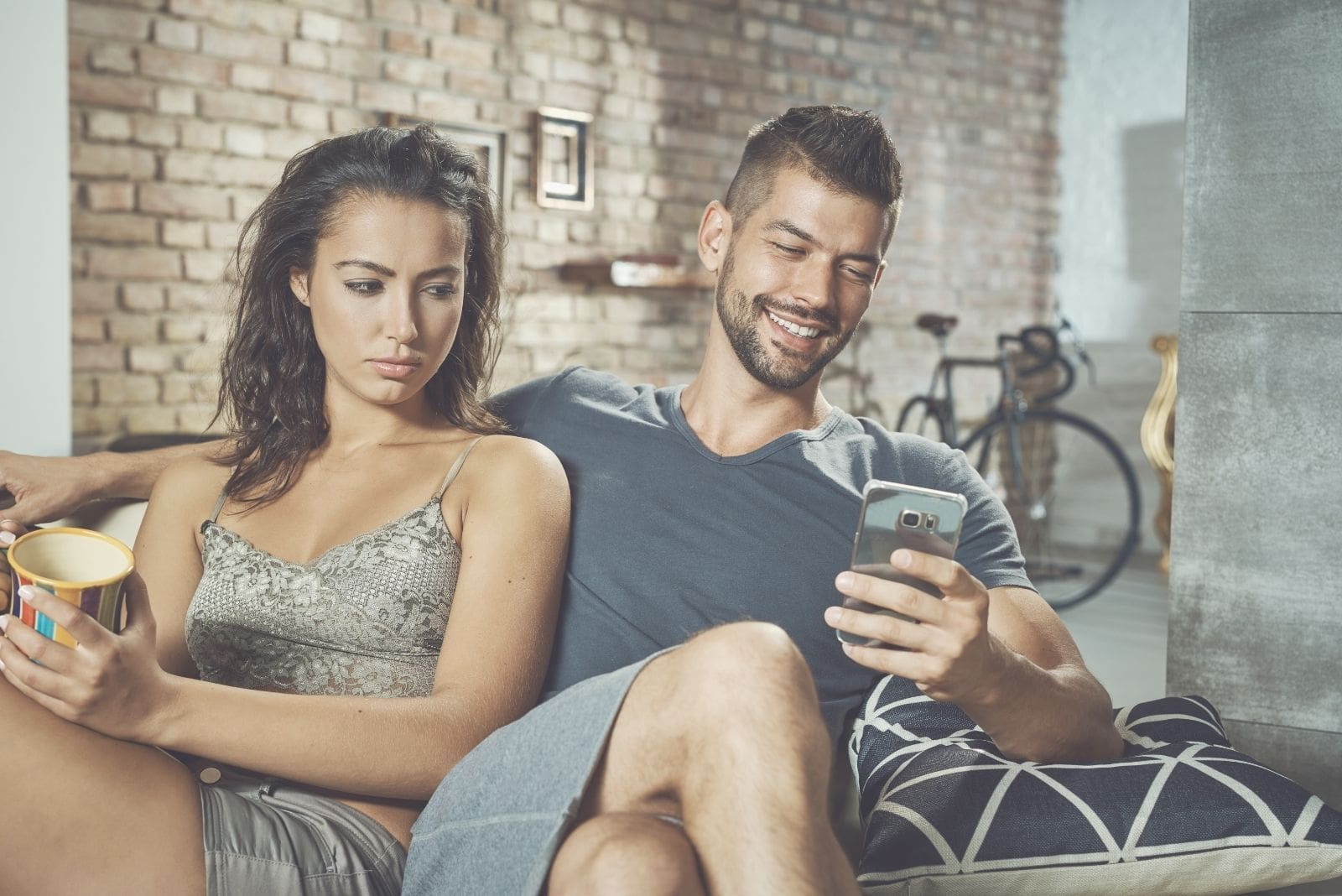 jealous woman sitting beside a happy man texting with legs crossed inside the living room